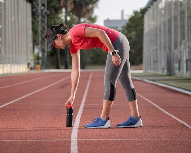 Mulher vista frontal se exercitando no campo