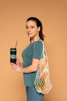 Mulher vista lateral com bolsa de tartaruga e garrafa térmica