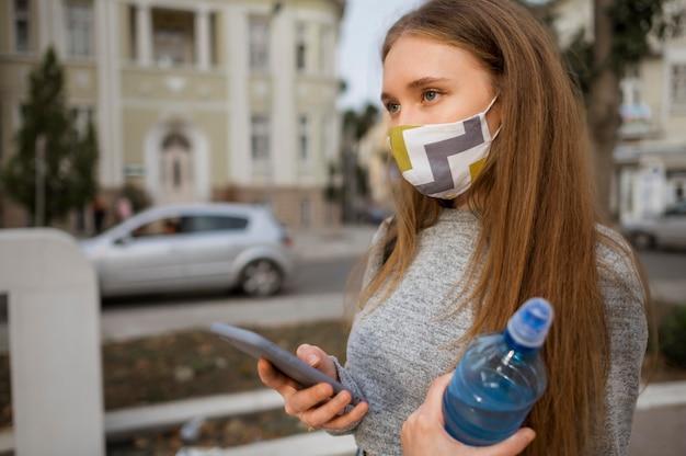 Mulher vista lateral com máscara médica segurando uma garrafa de água