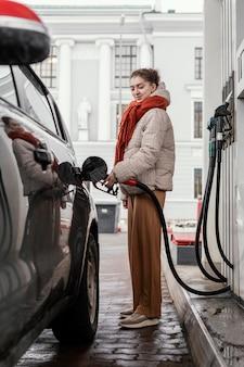 Mulher vista lateral em posto de gasolina