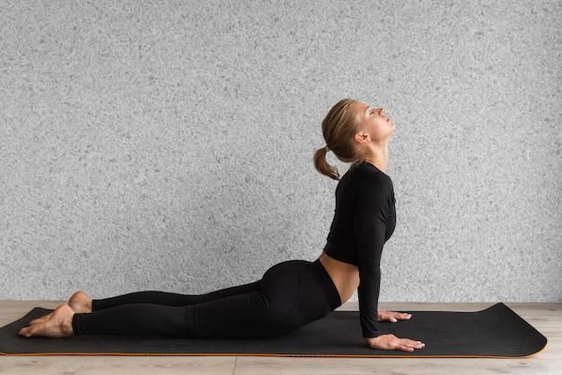 Mulher vista lateral fazendo pose de cobra