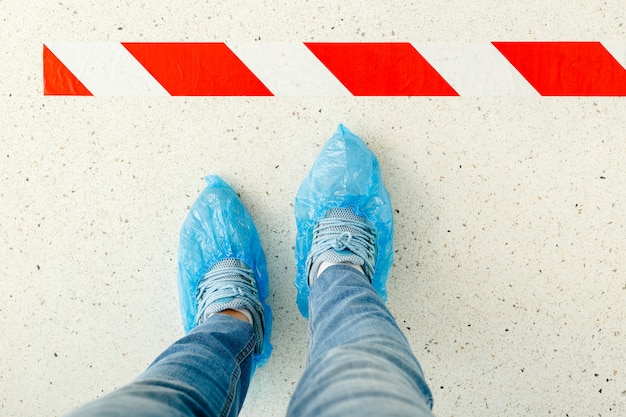 Mulher vista na fila mantendo distância social vestindo galochas, capas de sapatos médicos no hospital. distanciamento social. pernas em linha
