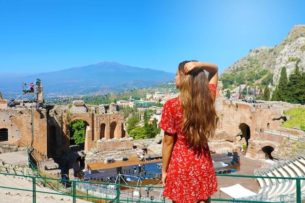 Mulher vista sobre ruínas do teatro grego em taormina com o vulcão etna, na sicília