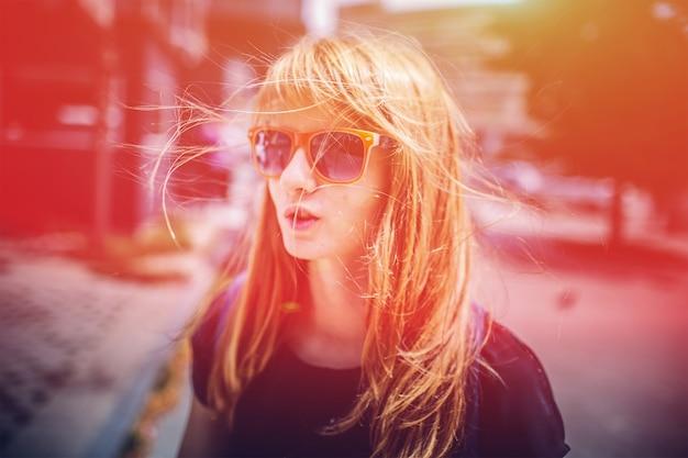 Mulher vivaz na cidade com lindos óculos iluminados pelo brilho do sol em uma rua movimentada com o centro