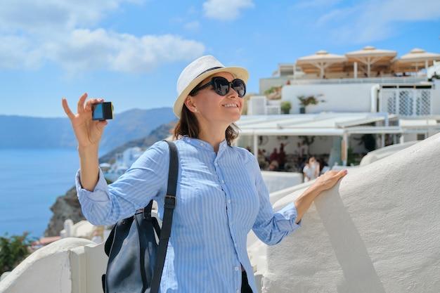 Mulher vloger de viagem viajando na vila grega de oia, na ilha de santorini, filmando um vídeo com a câmera aktion, arquitetura de fundo branco, mar, céu nas nuvens