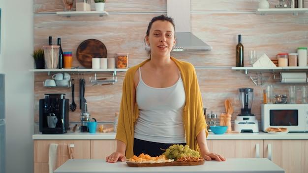 Mulher vlogger influenciadora sentada na cozinha de casa e falando olhando para a câmera. influenciador falando, fazer bate-papo por vídeo, videoconferência, gravar vlog de estilo de vida, visualização de webcam