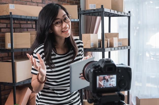 Mulher vlogging na frente da prateleira de pacotes