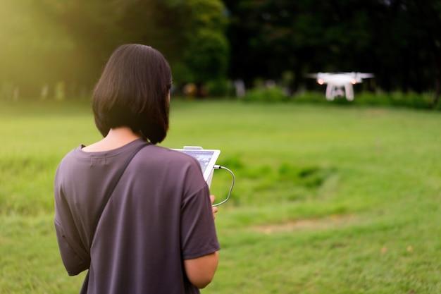 Mulher voando drone quadcopter no jardim