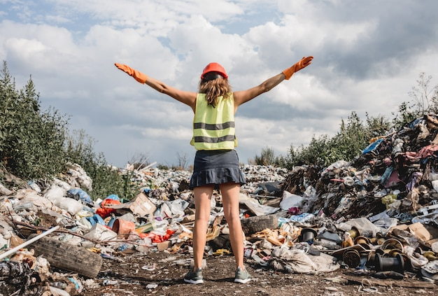 Mulher voluntária ajuda a limpar o campo de lixo plástico. dia da terra e ecologia.