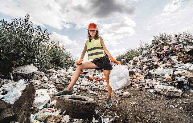 Mulher voluntária ajuda a limpar o campo de lixo plástico e pneus velhos. dia da terra e ecologia.