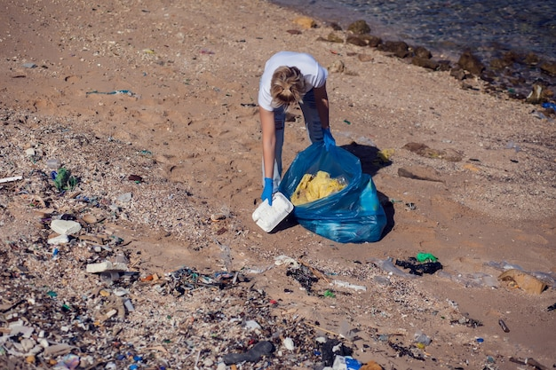 Mulher voluntária com um grande saco azul, coletando lixo na praia. conceito de poluição ambiental