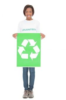 Mulher voluntária sorridente segurando sinal de reciclagem