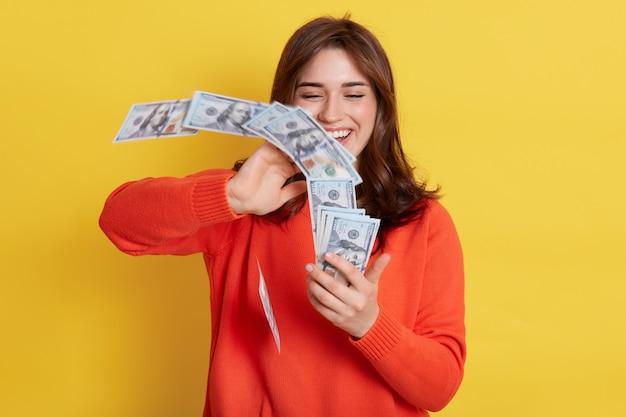 Mulher vomita em dinheiro no ar, rindo alegremente, segurando uma grande quantia de dinheiro, tendo recompensa pelo trabalho, vestindo jumper laranja, senhora rica ganhando na loteria, posando com moeda isolada sobre parede amarela.