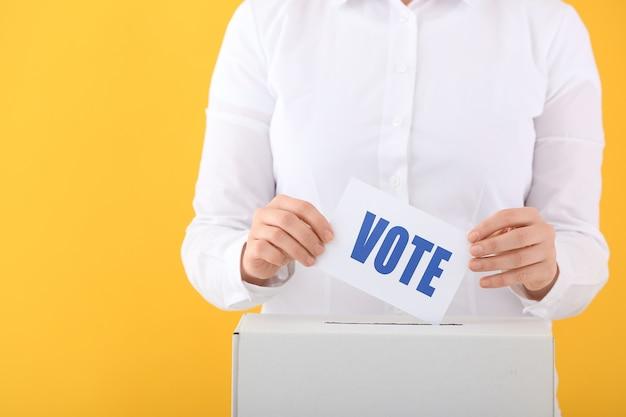Mulher votando perto da urna na superfície colorida