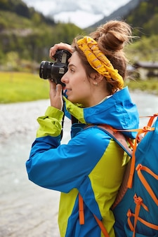 Mulher wanderlust caminha em prados verdes nas montanhas, tira fotos maravilhosas com câmera digital, aprecia a beleza da paisagem natural, usa jaqueta
