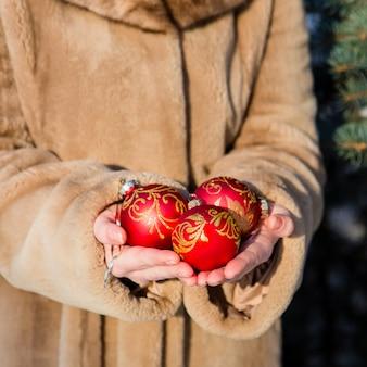 Mulher, weared, em, casaco pele, segurando, em, seu, mãos três, natal vermelho, bolas, close-up