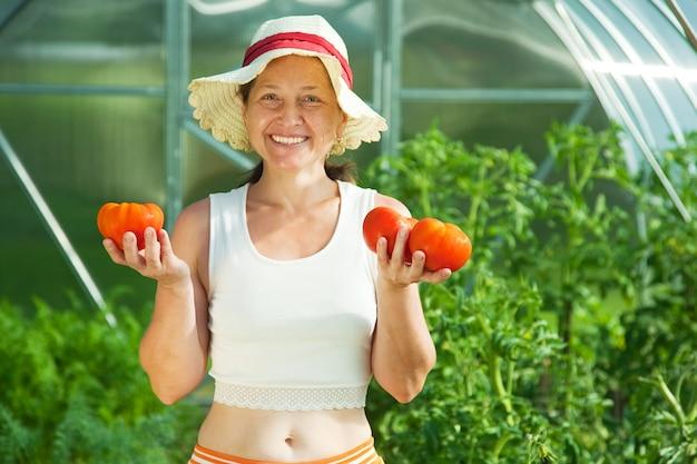 Mulher witrh tomate em estufa