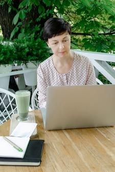 Mulher xícara verde matcha latte café chá local de trabalho cafe terassa 50 plus freelancer