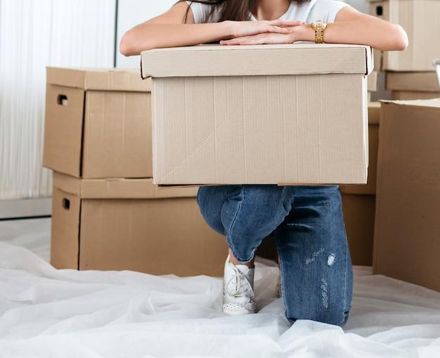 Mulher ypung com uma caixa de papelão sentada no chão em um apartamento novo