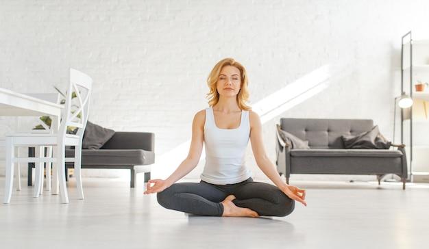 Mulher yuong sentada no chão em pose de ioga, interior da sala em tons de branco
