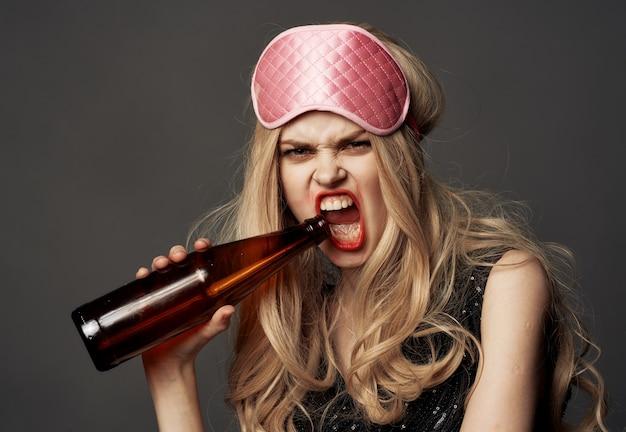 Mulher zangada com uma garrafa de cerveja na mão