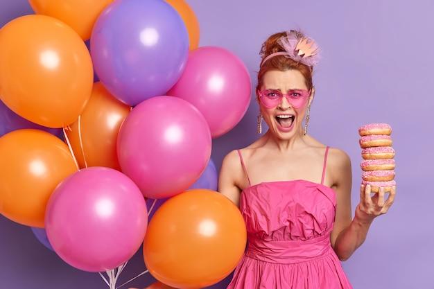 Mulher zangada e irritada com um vestido festivo rosa e óculos de sol em forma de coração segurando uma pilha de donuts, exclamando em voz alta poses com balões de hélio multicoloridos