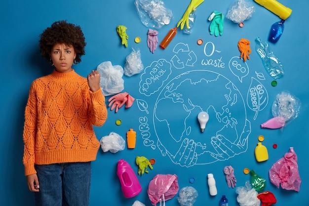 Mulher zangada e irritada pede para evitar poluição, mostra punho, exigindo das pessoas serem ecologicamente corretas, tem olhar severo, planeta desenhado e muito lixo plástico demonstrando grave problema