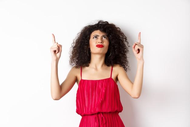 Mulher zangada e mal-humorada com cabelo encaracolado, usando um vestido vermelho, carrancuda e olhando para cima desapontada, em pé sobre um fundo branco.