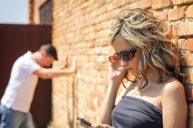 Mulher zangada em foco, olhando para o telefone e um homem frustrado, colocando as mãos em uma parede ao fundo