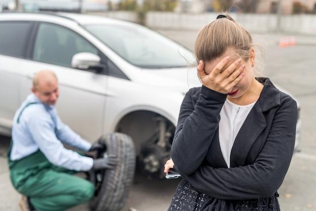 Mulher zangada no serviço de carro com carro quebrado