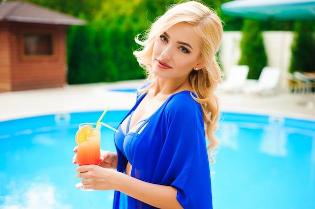 Mulheres a beber cocktails na piscina. retrato das jovens mulheres bonitas que bebem o cocktail na beira da piscina.