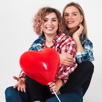 Mulheres abraçadas posando com balão para dia dos namorados