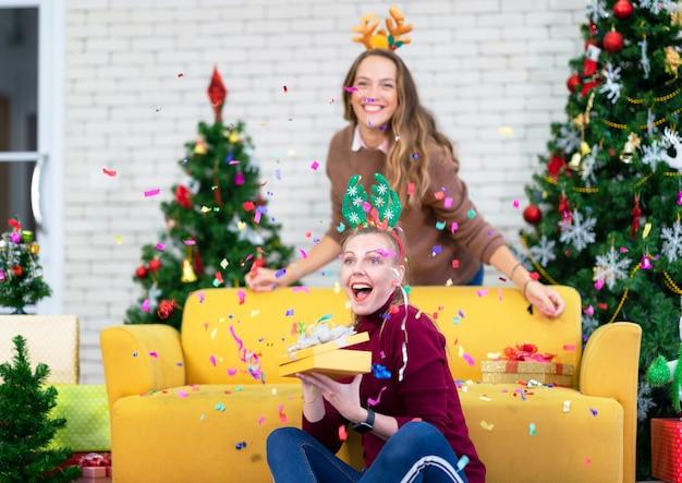 Mulheres abrindo a caixa de presente de natal com um amigo. conceito de família de férias de natal.