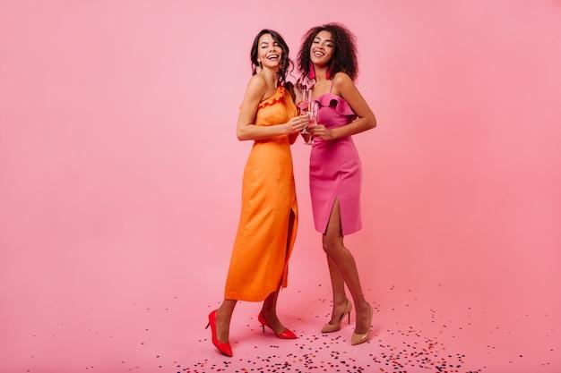 Mulheres adoráveis com vestido laranja comprido gostando de fotografar