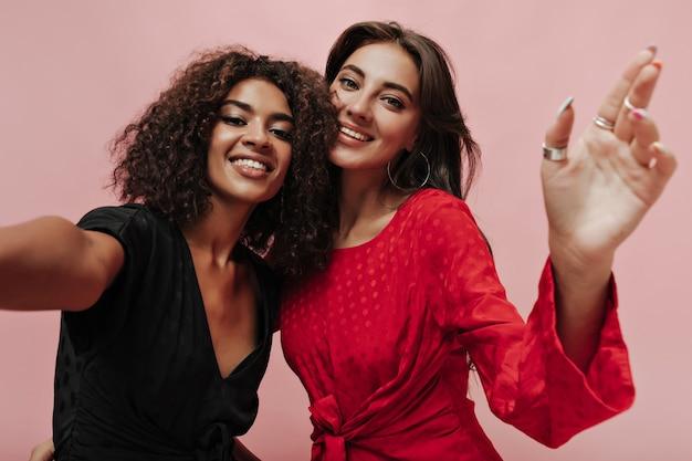 Mulheres adoráveis de bom humor com penteado estiloso em vestidos brilhantes de bolinhas sorrindo e tirando fotos na parede isolada