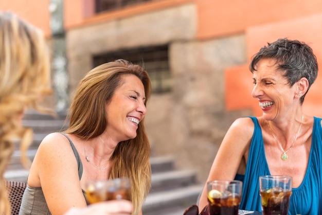 Mulheres adultas de meia-idade, desfrutando de bebidas em um bar ao ar livre. mulheres adultas rindo e se divertindo.