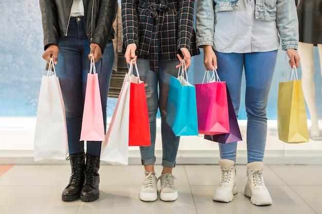 Mulheres adultas segurando sacos coloridos