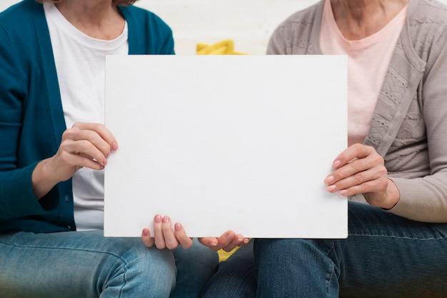 Mulheres adultas segurando um cartaz de maquete