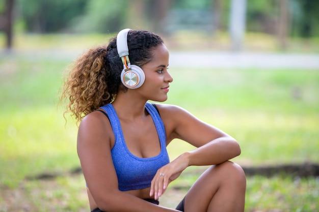 Mulheres afro-americanas de raça mista sentado no parque com fone de ouvido