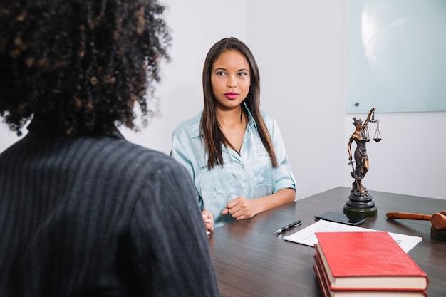 Mulheres afro-americanas, sentado à mesa perto de documento, caneta, figura e martelo