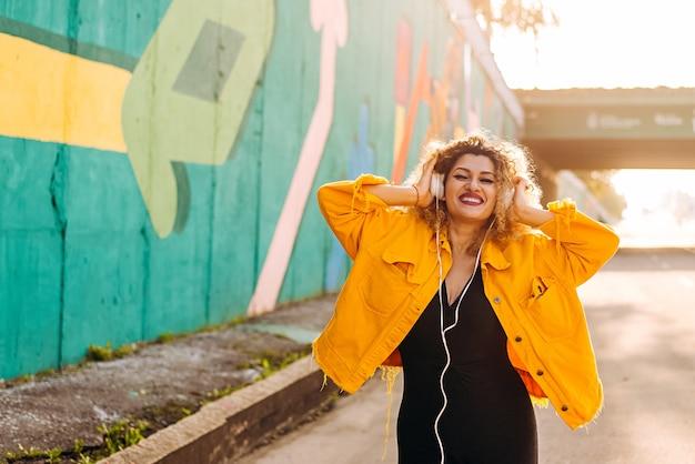 Mulheres afro-positivas ouvem música em fones de ouvido no colorido estilo wall street