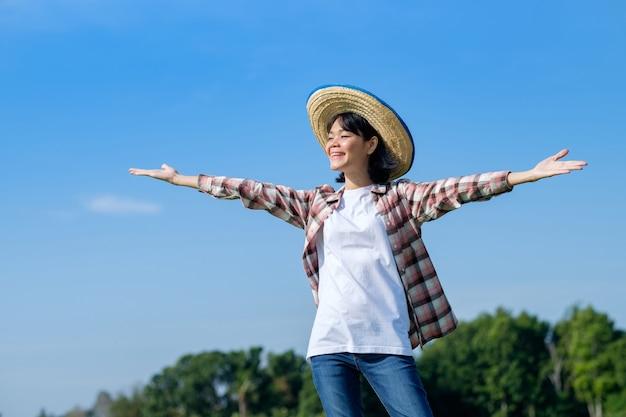 Mulheres agricultoras asiáticas sorriem e levantaram as mãos com o céu azul.