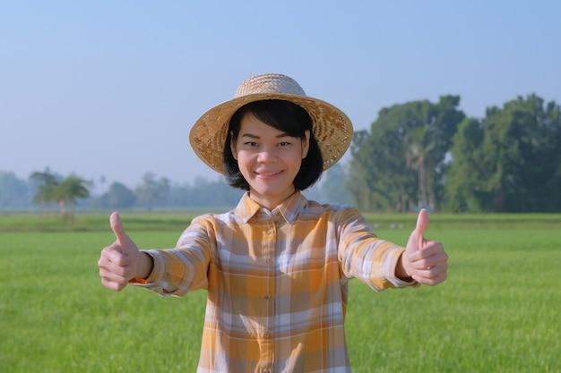 Mulheres agricultoras asiáticas usam camisa amarela e sorriem na fazenda verde.