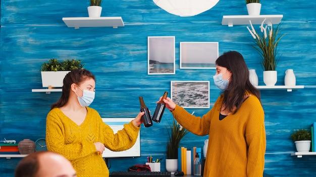 Mulheres alegres com máscara protetora discutindo na sala de estar sobre distanciamento social contra a propagação do vírus covid 19