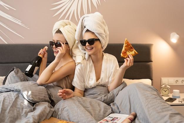 Mulheres alegres, deitadas na cama e segurando a garrafa de champanhe e uma fatia de pizza. namoradas usam óculos e toalhas de banho enroladas nas cabeças. conceito de festa de meninas em casa. interior do quarto em apartamento moderno