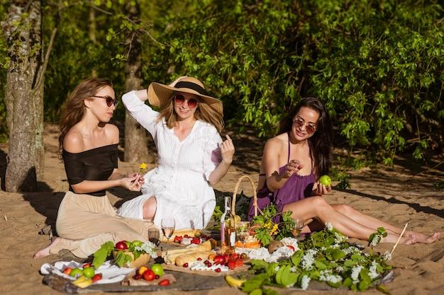 Mulheres alegres descansando na natureza com vinho