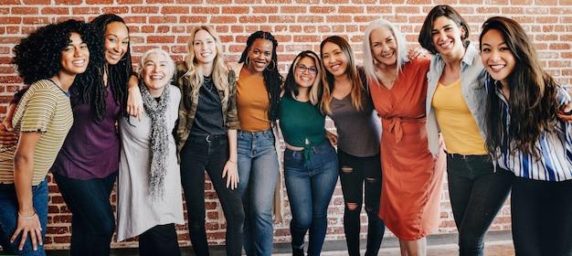 Mulheres alegres e diversificadas em frente a uma parede de tijolos vermelhos