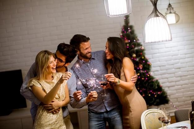 Mulheres alegres e homens comemoram véspera de ano novo com brilhos e vinho em casa