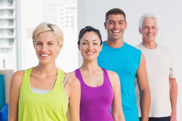 Mulheres alegres e homens em roupas esportivas no ginásio
