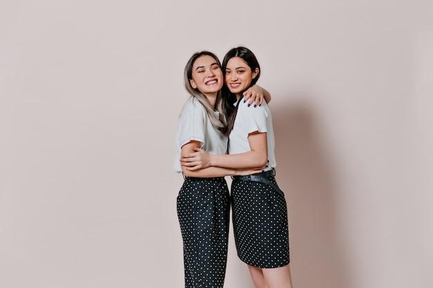 Mulheres alegres em camisetas brancas e saias de bolinhas se abraçando na parede bege